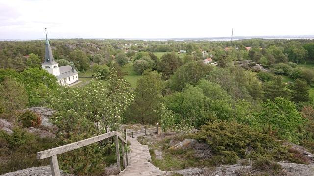 Utsikt över skog, hus och en kyrka