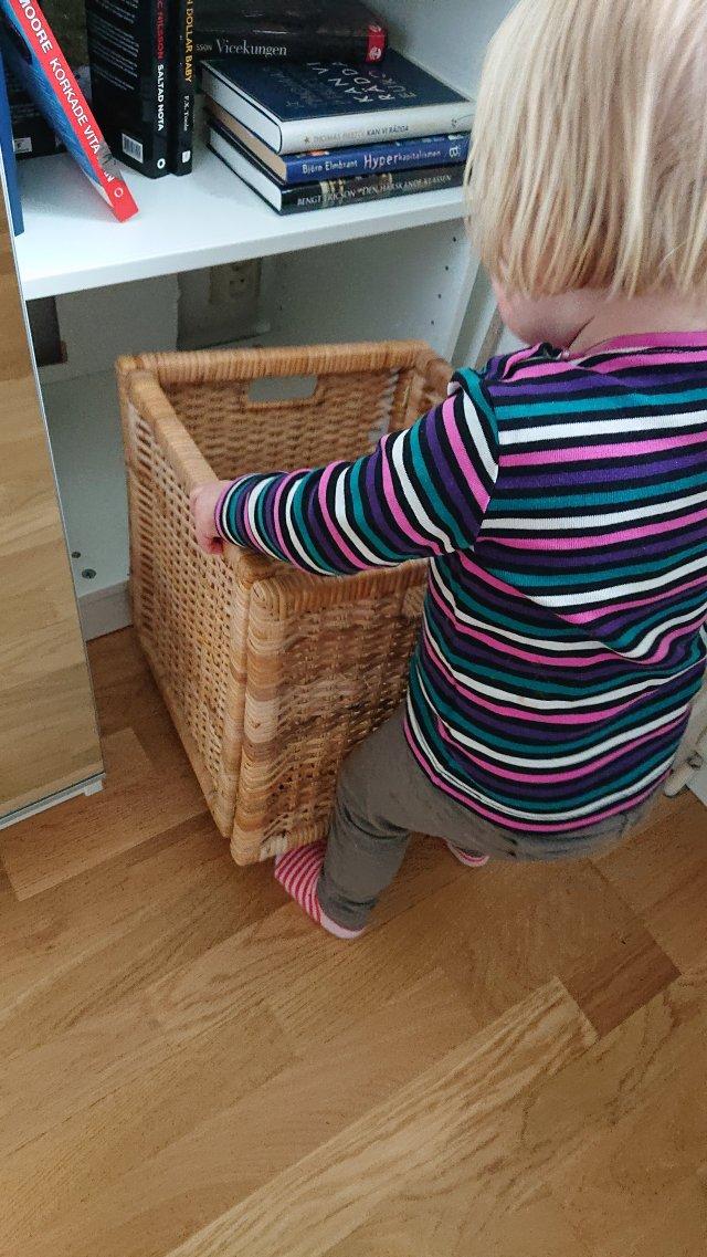 Olivia ställer in korgen i vårt sovrum efter att vi hängt ut kläder.
