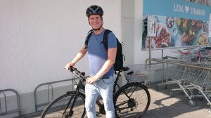 Johan vid cykeln med ryggsäck på ryggen och matvaror i cykelkorgen